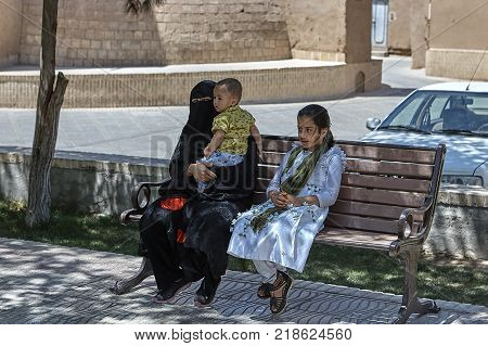 Yazd Iran - April 21 2017: An Arab family of three people sitting on a bench in a city park a woman in a black Islamic burqa with a baby boy and a 10 year old girl.