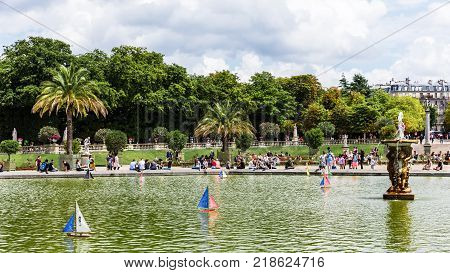 Paris France - Jule 11 2017: Colorful toy boats race on the water in a pond in the Luxembourg Gardens (Jardin du Luxembourg) one of the most beautiful gardens in Paris.