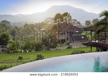 Panoramic view of rice terraces and mountains and the small pool in the foreground. Bali Indonesia