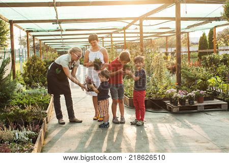 Female florist showing flowers to the customers at the flower store. Adorable little boy is shopping plants