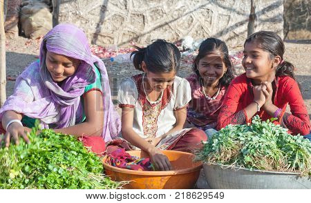 MAHARASHTRA, INDIA - JANUARY 10, 2016: Indian girls selling vegetables at local market