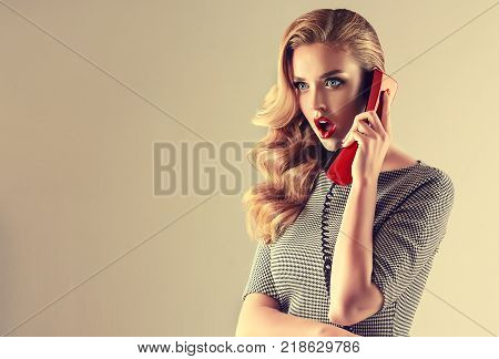 Beautiful woman in pin up style with vintage red phone.  Shocked  and happy pretty girl  . Presenting your product. Expressive facial expressions
