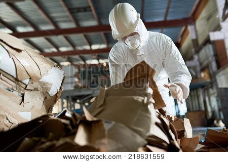 Portrait of  factory worker wearing biohazard suit sorting reusable cardboard on recycling plant, copy space