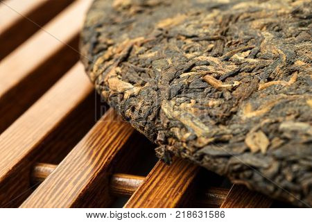 Old Shu Puerh Chinese fermented black tea on wooden tea-board, macro photo, selective focus