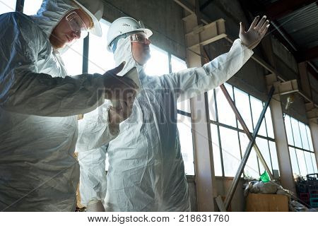 Portrait of two workers wearing biohazard suits standing in industrial warehouse of modern  plant against windows, copy space