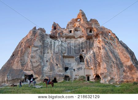 CAPPADOCIA, TURKEY - MAY 16, 2016: Couple of horseback riders with guide walking in Red valley, Cappadocian region, Central Anatolia