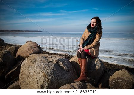 Young beautiful woman in elegant clothes with scarf sits on the coastline in winter season and looking at camera. 1 person