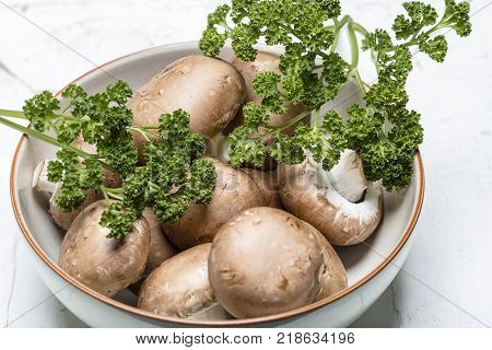 Brown mushrooms in a bowl with parsley - Close up