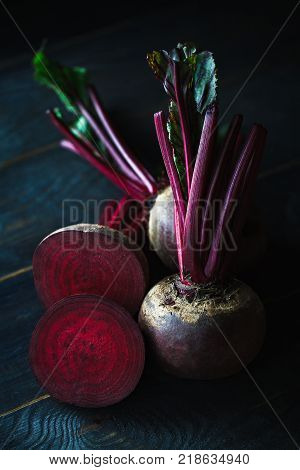 Organic beet root with green leaves on old wooden. mystic light