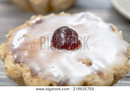 Marzipan cake with sugar glaze and candied cherry