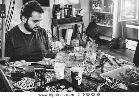 ISTANBUL, TURKEY : Portrait of jeweler making elements of decoration in workshop, forming and polishing it on work station with different tools on October 4, 2017