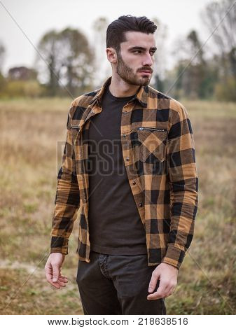 Portrait of sexy young man looking to a side near wooden fence in countryside next to a field or grassland