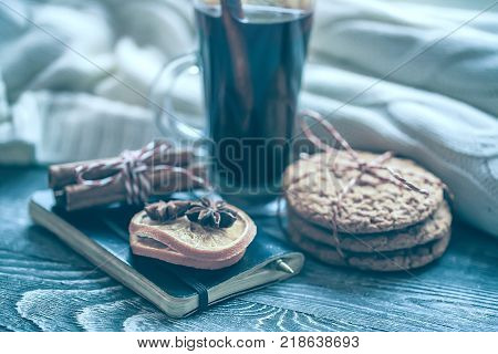 New Year winter still life: warm woolen knitting, hot mulled wine, cinnamon, Christmas cookies and orange. Hygge style. Cozy winter home morning holiday. Soft photo. Selective focus