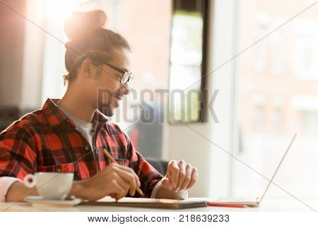 Happy young Hispanic man watching online conference and making notes in notepad