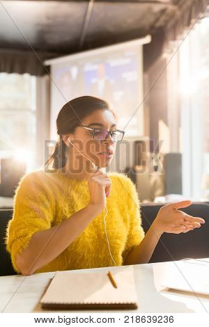 Modern girl with earphones video-calling in cafe after organization of work