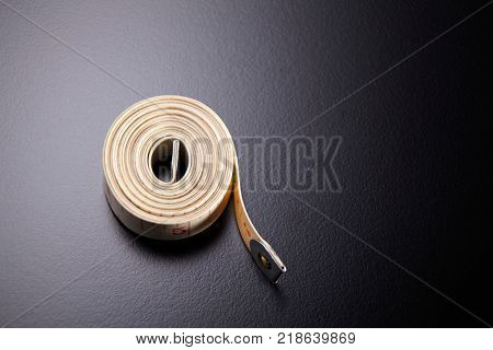 rolled tape measure on the black background