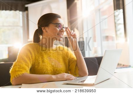 Young attractive and elegant female talking through video-chat while sitting in cafe