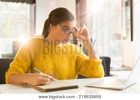 Young businesswoman or student watching webcast in cafe and making notes