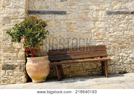Wooden bench and flower in pot in Omodos village Cyprus
