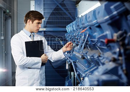 Young mining farm engineer in whitecoat checking quality of new cryptocurrency transaction equipment