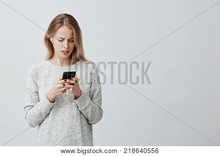 Amazed dissatisfied woman with dyed blonde hair dressed casually with white earphones holding her modern smartphone recieving message being shocked to forget about important meeting with businesspartners