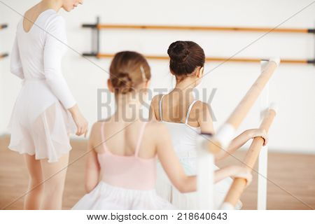 Rear view of little ballerinas holding by bar and making exercise with teacher