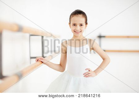 Happy little ballerina looking at camera while training before stage performance