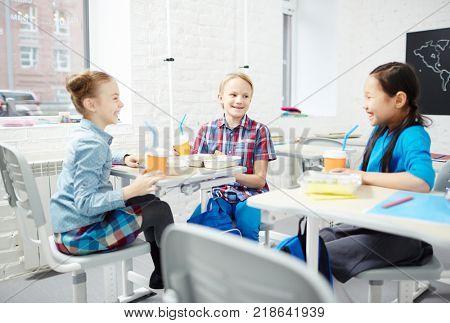 Three friendly schoolmates having talk during lunch in classroom at break