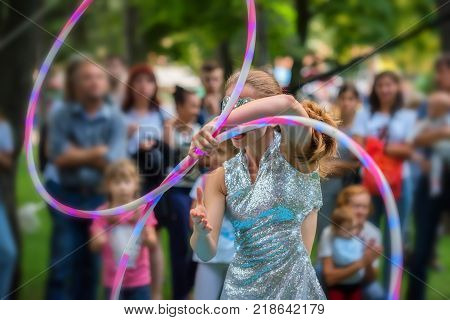 Back view teenage girl in beautiful dress plays with hula hoops outdoors