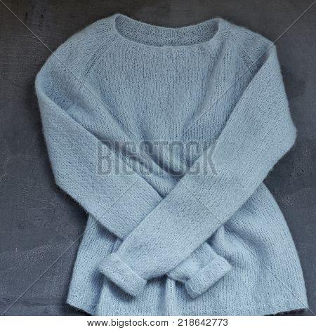 Pastel blue knitted woolen sweater on a hanger
