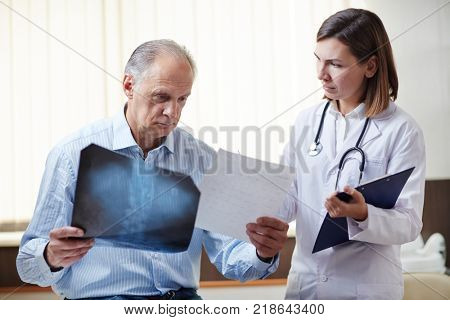 Young doctor showing x-ray image to sick retired patient and giving him recommendations about medical treatment