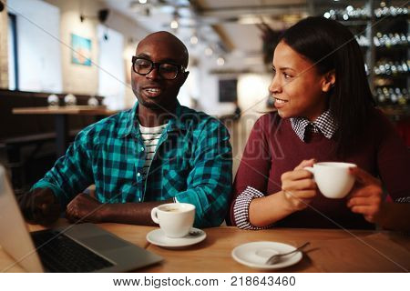 Two intercultural businesspeople having coffee in cafe and talking at meeting