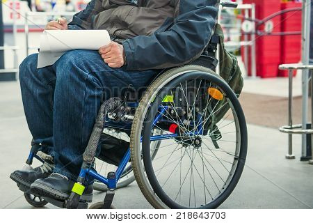 No face disabled, handicapped person on wheeled chair fills the form blank or makes a shopping list in the market place. Selective focus. Space for text.