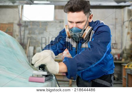 Portrait of mature modern man wearing respirator repairing boat in yacht workshop using electric polishing tool, copy space
