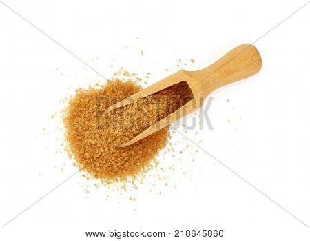 Close up one wooden scoop spoon full of raw brown cane sugar with pinch spilled and spread around isolated on white background elevated top view directly above