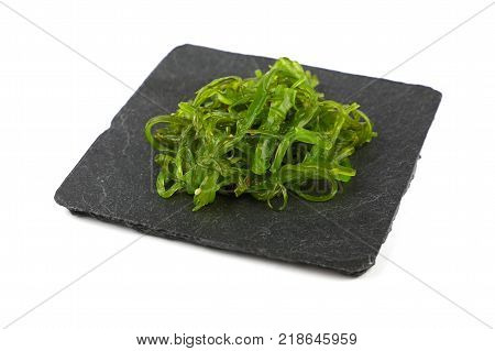 Close up portion of green wakame seaweed salad on square black slate board plate isolated on white background high angle view
