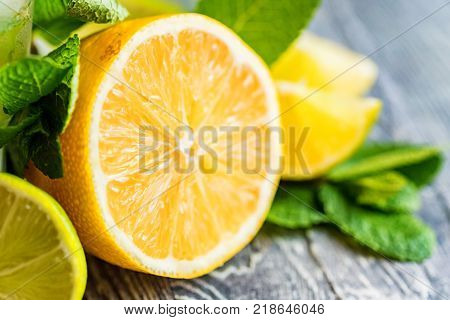 Very close up of ripe cut lemon, lime and mint. Lemonade ingredients. Freshness and health concept. Selective focus. Extremly short field of depth