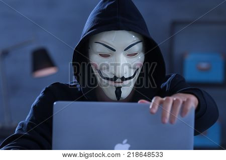 MYKOLAIV, UKRAINE - SEPTEMBER 29, 2017: Anonymous person in Guy Fawkes mask using laptop indoors