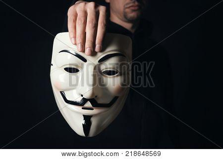 MYKOLAIV, UKRAINE - SEPTEMBER 29, 2017: Man holding Guy Fawkes mask on black background