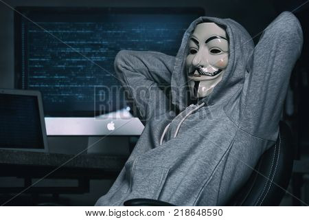 MYKOLAIV, UKRAINE - SEPTEMBER 29, 2017: Anonymous person in Guy Fawkes mask near computer indoors