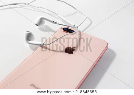 KIEV, UKRAINE - OCTOBER 23, 2017: iPhone 8 Plus Gold with headphones on light background, closeup