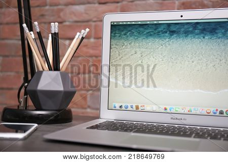 KYIV, UKRAINE - NOVEMBER 10, 2017: Apple MacBook Air Silver with home screen on table, closeup