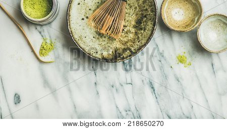 Flat-lay of Japanese tools and bowls for brewing matcha tea. Matcha powder in tin can, Chashaku spoon, Chasen bamboo whisk, Chawan bowl, cups for ceremony, grey marble background, top view, copy space