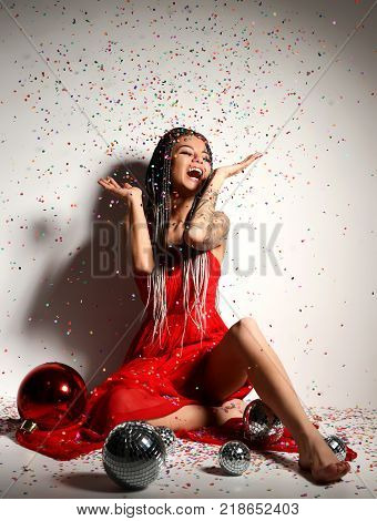 Young beautiful sexy woman in elegant red dress sitting with christmas decoration ball and confetti. New year Holidays celebration concept party