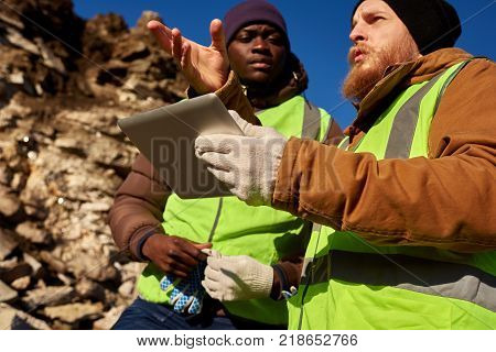 Low angle portrait of two industrial workers wearing reflective jackets, one of them African, inspecting mineral mines on worksite outdoors and using digital tablet