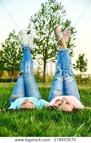 Two happy young girls lie on the grass with their legs up