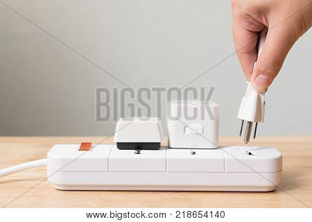 Hand of male or female unplugged plug into socket to save energy Reduce energy efficiency concept
