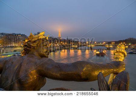 PARIS - December 10 2017: Eiffel Tower and Alexandre III Bridge at night  in Paris, France. Alexander the Third bridge is popular touristic site in Paris