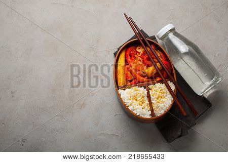 Wooden lunch boxe with healthy food ready to go for work or school, ahead meal preparation or dieting concept. On a old stone table with rust. Top view with copy space.