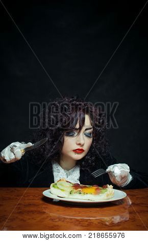 Photo of young aristocratic girl preparing to eat her fruit dessert with fork and knife over dark background.